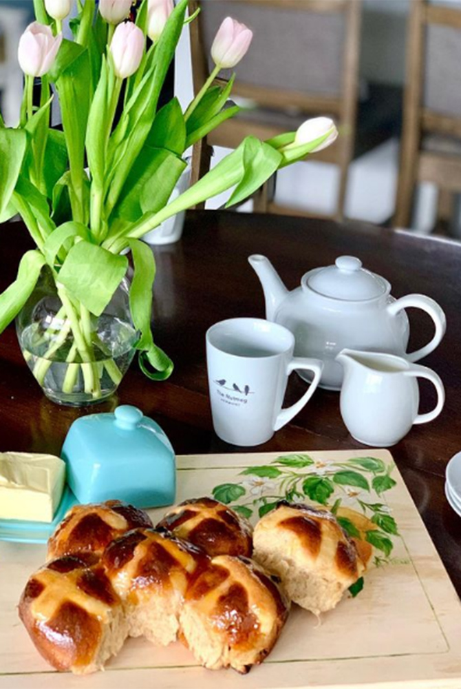 bread, tea, and tulips on a table
