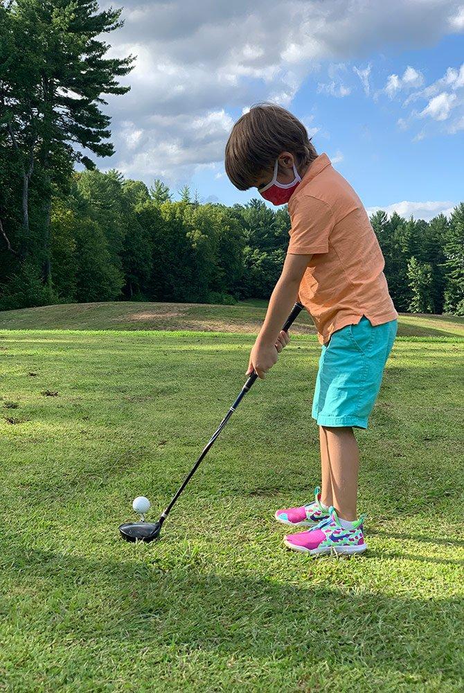 child wearing mask playing golf