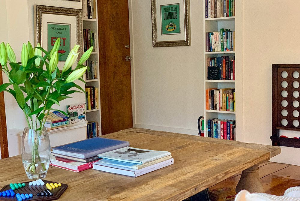 coffee table with books and games and a vase with flowers
