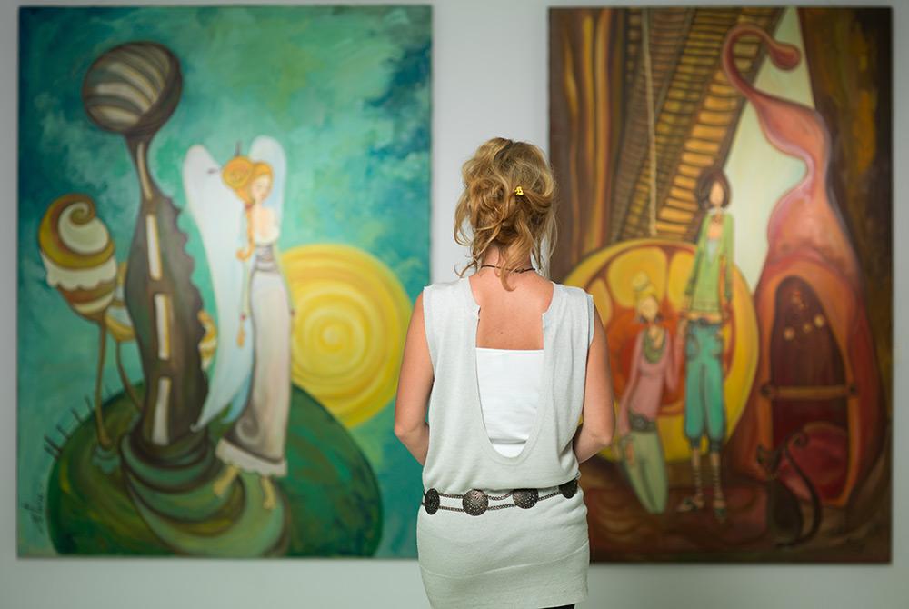 woman looking at museum paintings
