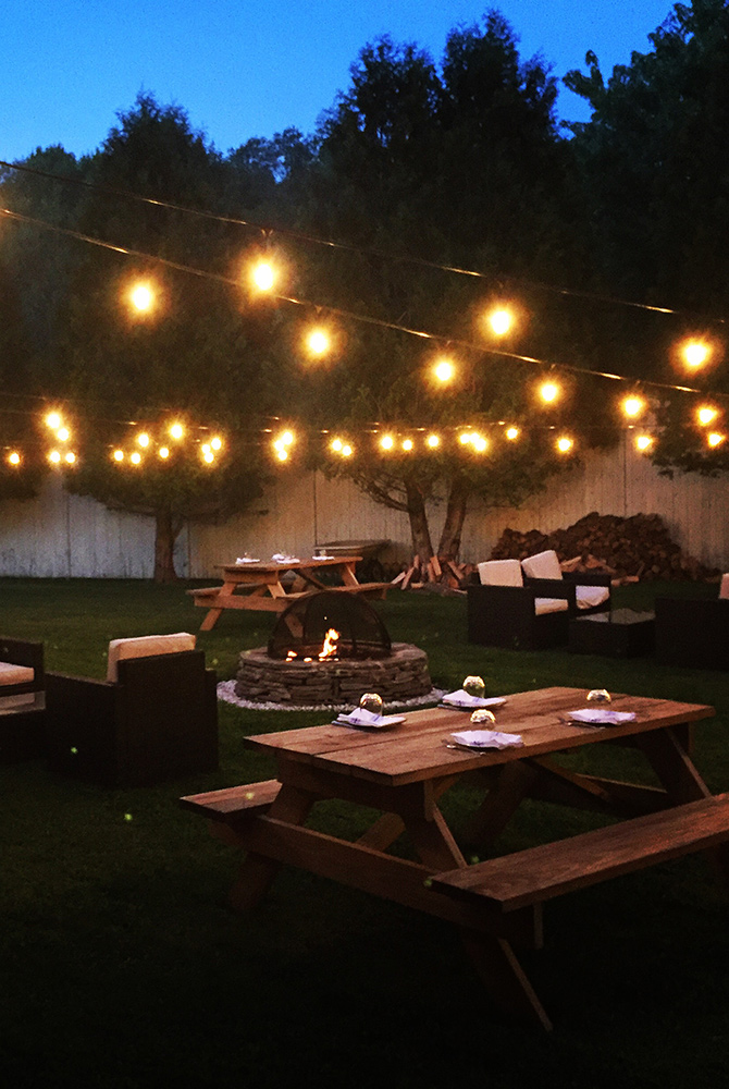 outdoor dining area with lights and firepit