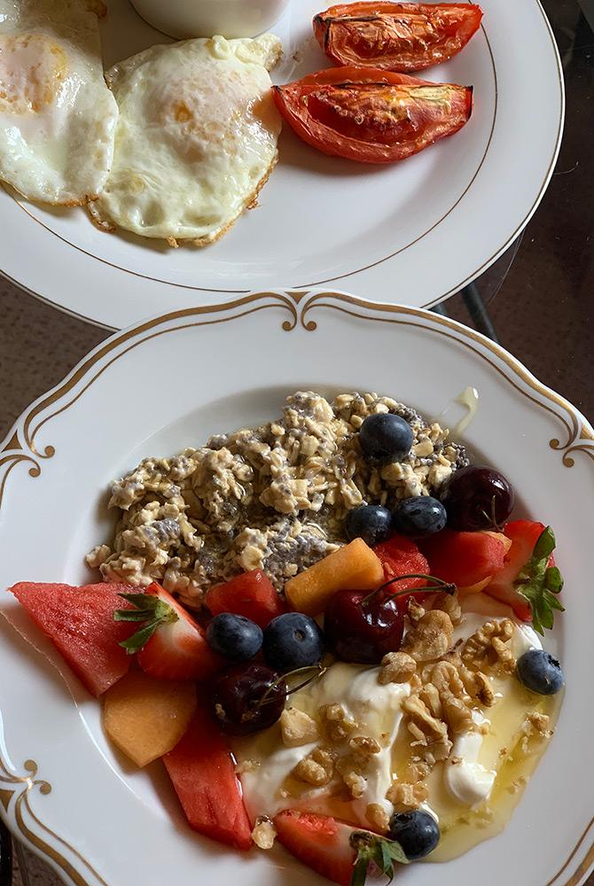 breakfast with eggs, tomatoes, oats, fruit, and yogurt
