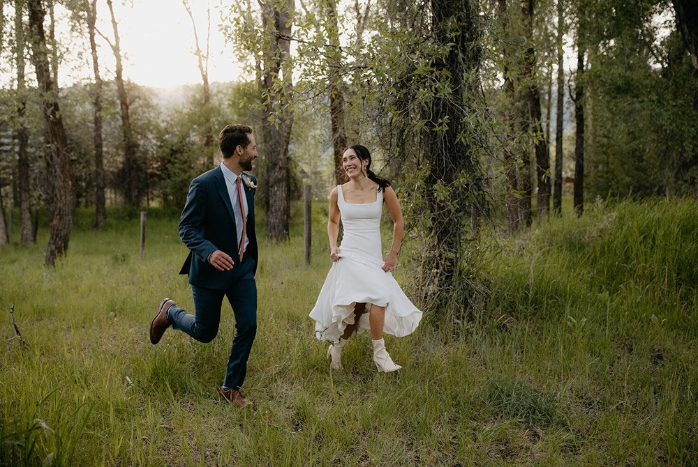 Wedding couple running through the forrest together