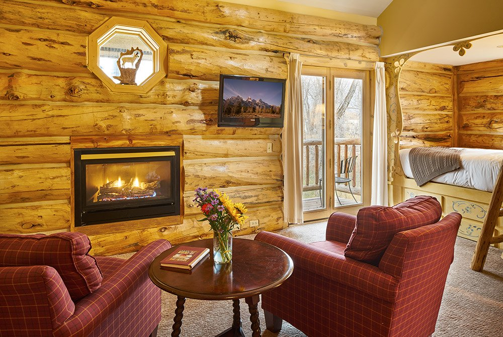 View of rustic room with fireplace and two arm chairs