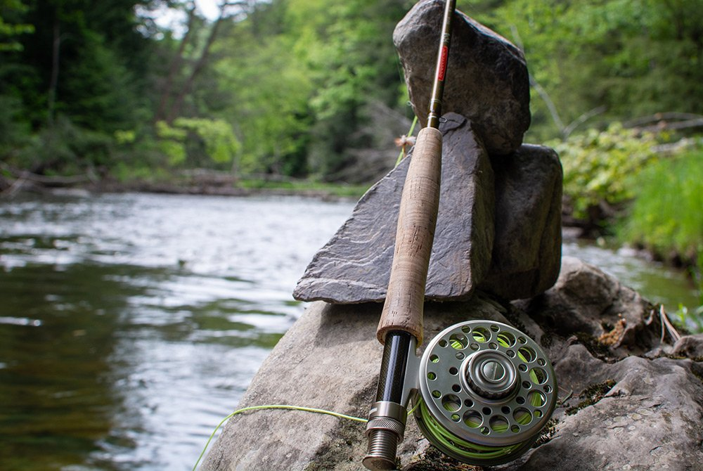 Fly fishing rod next to river