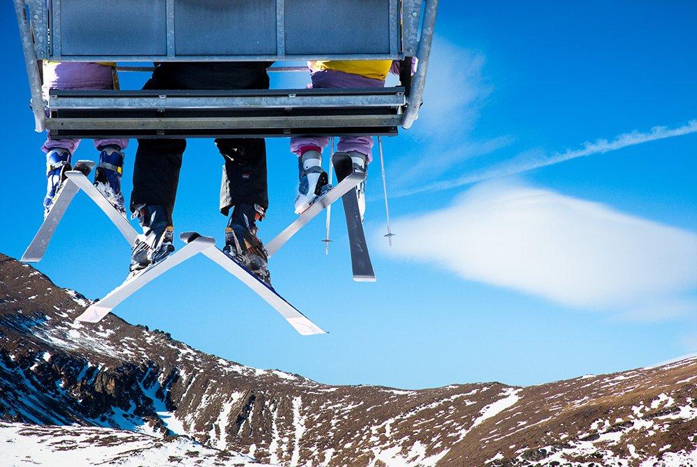 Three people sitting on ski lift