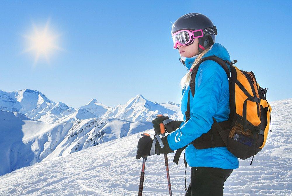 Women standing on mountain about to ski