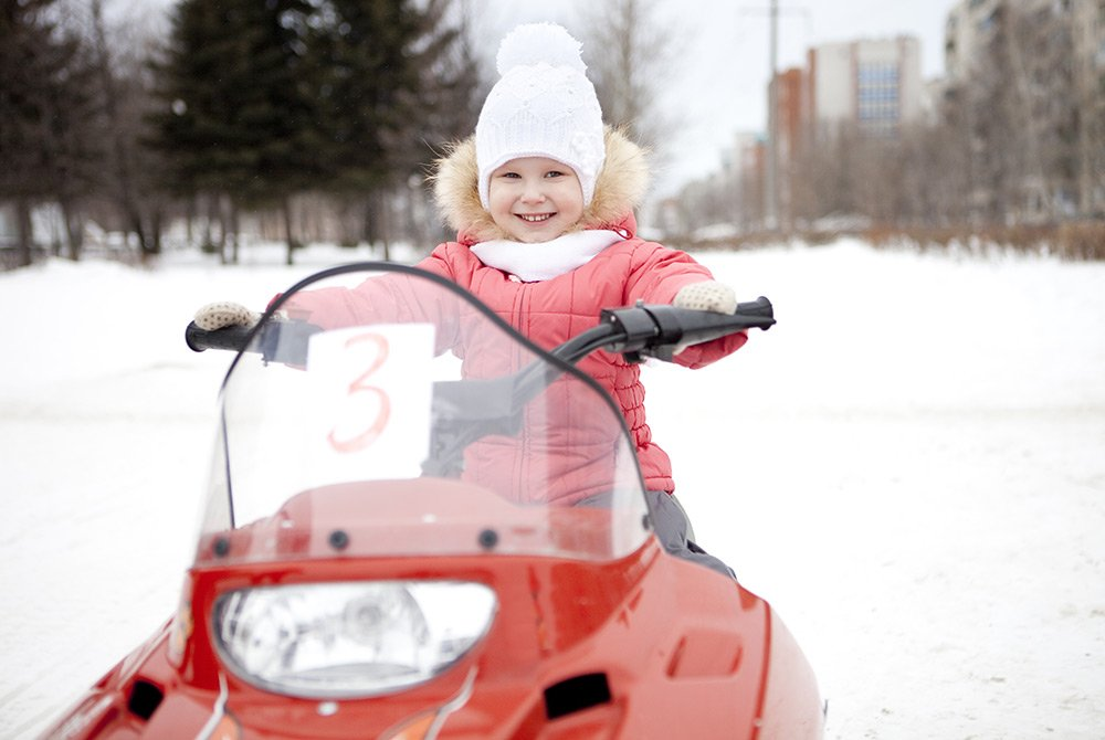 Child sitting on snow mobile