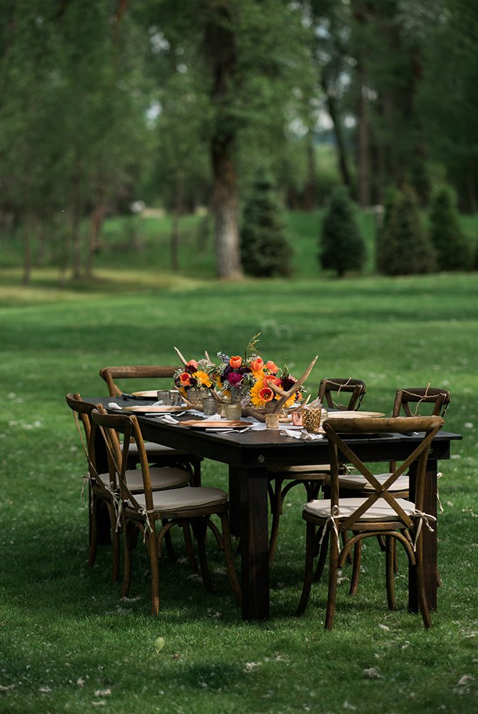 Set table and chairs in grassy field