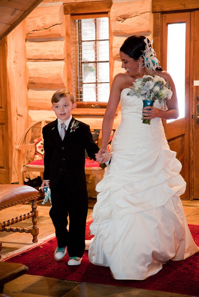 Young boy holding hands with the Bride