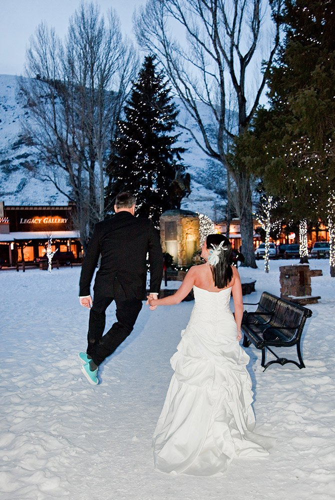 Married couple facing away from camera holding hands while groom hops into air