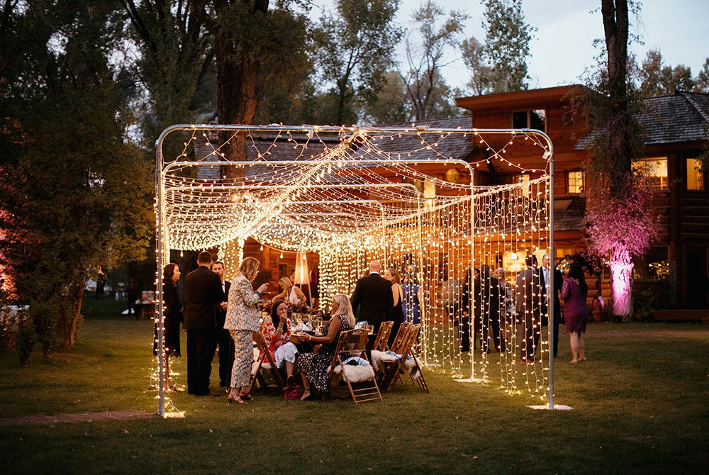 View of gathering in evening with decorative lighting outside