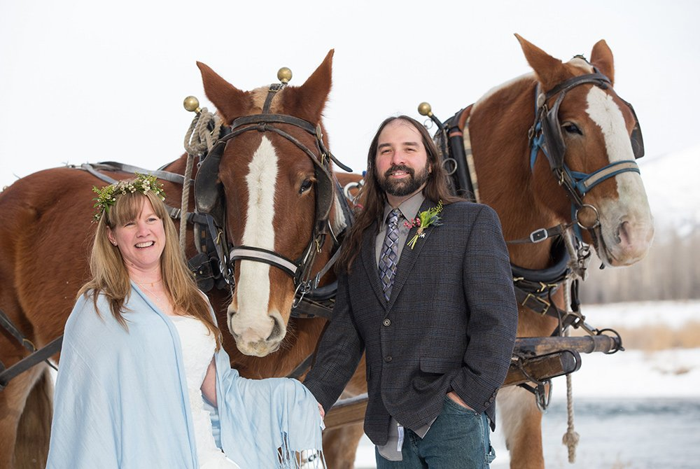 Married couple posing with horses