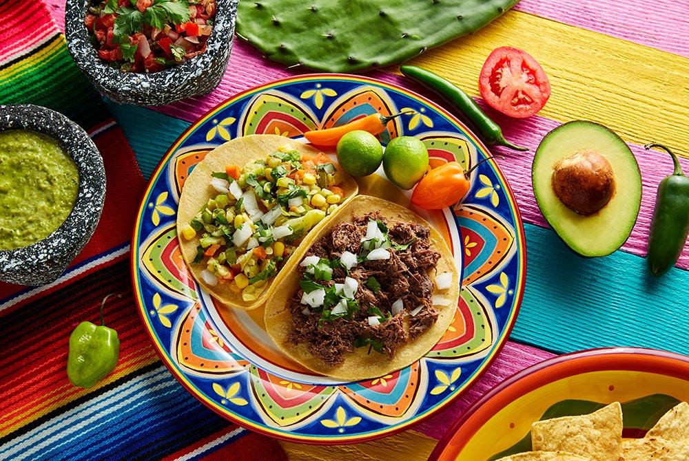 Street tacos next to guacamole and pico de gailo