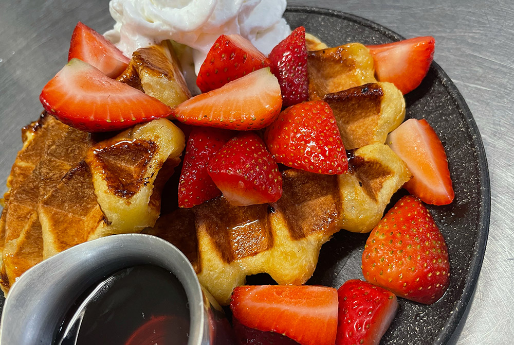 Strawberries and whipped cream on waffles