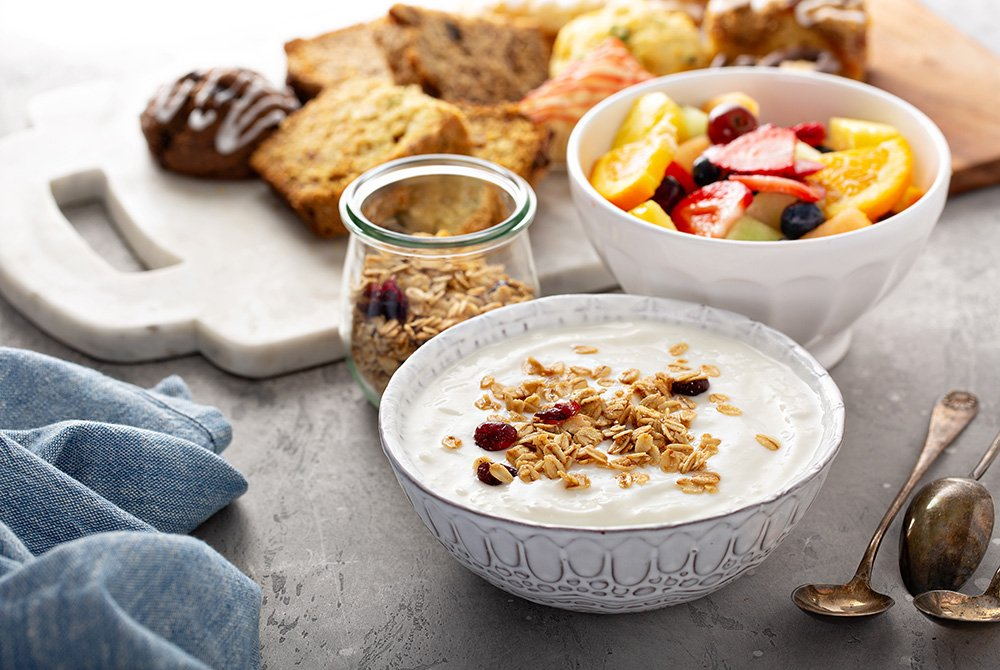 Bowl of yogurt, fruit, and tray of bread