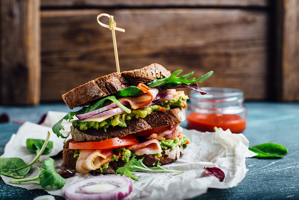 Double stacked bacon avocado sandwhich on wheat bread