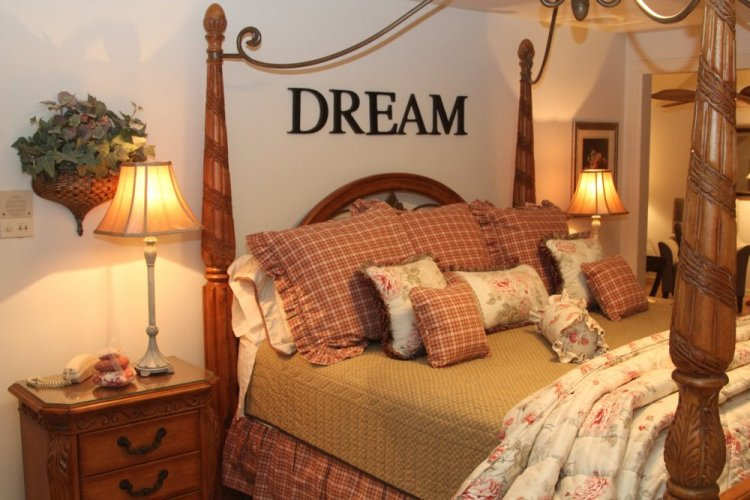 A four poster bed with the word dream on the wall nearby