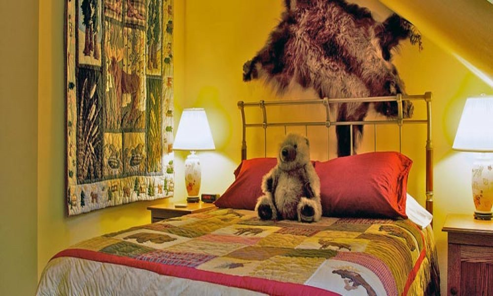 A Queen Bed with night stands, lamps, and a teddy bear