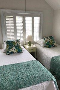 Twin beds infront of window in bedroom