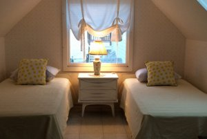 Twin beds next to each other under vaulted ceiling