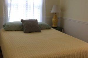 Queen bed infront of window in bedroom