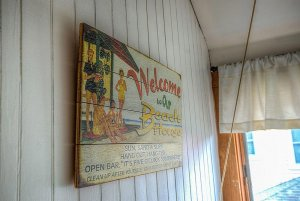 Wood beach sign hung on outdoor wall