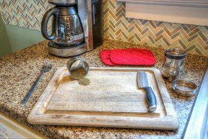 Cutting board on counter next to coffee maker