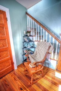 Rocking chair and blanket next to staircase