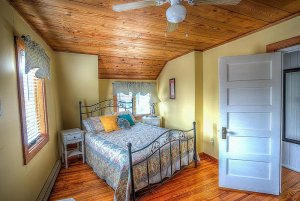 Queen-sized bed in room with windows and ceiling fan