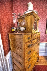 Wine glasses and bottles on wood dresser with mirror