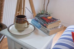 Books and mug on small table by couch