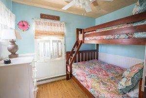 Bunk bed with ladder next to window and dresser