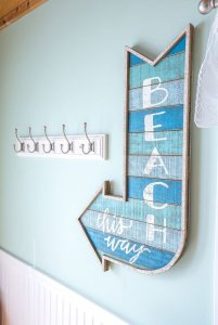 Beach arrow wall decoration next to coat rack