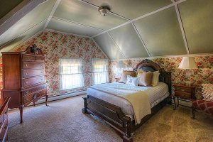 Queen-bed and dresser in bedroom with vaulted ceiling