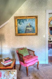 Cushioned seat under portrait under vaulted ceiling