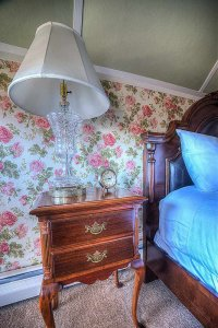 Bedside table, lamp, and clock next to bed