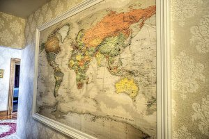 Large map of the world hung on wall