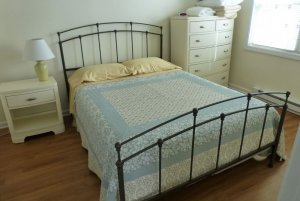 Queen-sized bed between dresser, window, and bedside table