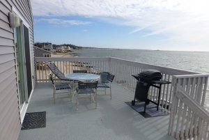 Chairs and table by grill on deck