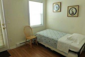 Twin bed infront of window, door, and pictures