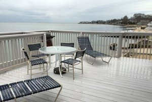 Beach chairs on wood deck above shore