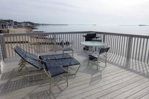 Reclining beach chairs infront of grill on wood deck