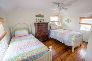 Twin beds separated by dresser in bedroom