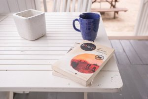 Mug and books on porch table outside