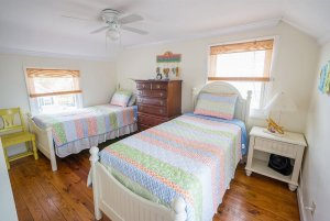Twin beds by windows and dresser
