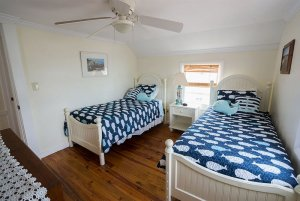 Twin beds under ceiling fan and window
