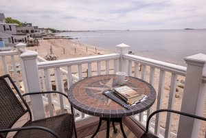 Books and mug on table next to fence overlooking beach