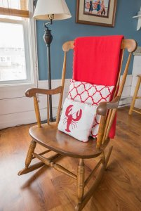 Rocking chair with pillows and blanket by lamp