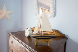 Model boat and clock on dresser
